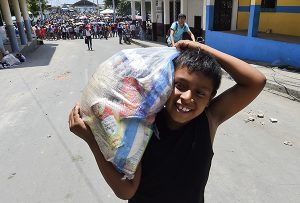 A boy smiles after receiving food supplies in Manta, Ecuador on April 20, 2016.  The death toll from Ecuador's earthquake was set to rise sharply after authorities warned that 1,700 people were still missing and anger gripped families of victims trapped in the rubble. A 6.1-magnitude earthquake struck off the coast of Ecuador Wednesday, sowing new panic four days after a more powerful quake killed more than 525 people, with hundreds still missing. / AFP PHOTO / LUIS ACOSTA -----