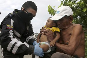 A highway police doctor checks on a baby who's family was affected by the 7.8-magnitude earthquake that hit Ecuador's Pacific coast, at a road side in Canaveral, Ecuador, Thursday, April 21, 2016. President Rafael Correa said Ecuador's worst earthquake in decades caused billions of dollars of damage and he is raising sales taxes and putting a one-time levy on millionaires to help pay for reconstruction. (AP Photo/Dolores Ochoa) -----