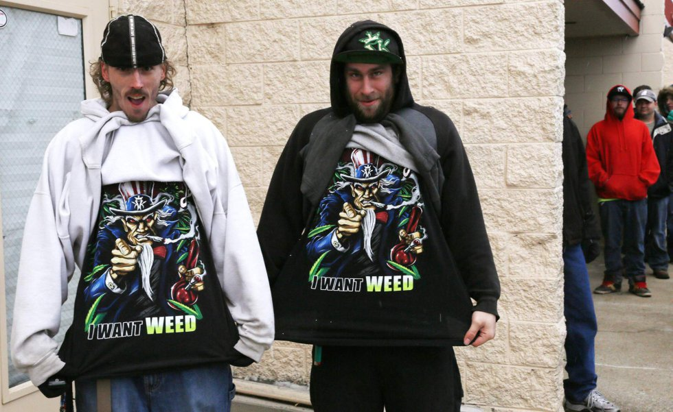 """Mark Gordon (left) and Ryan Perry show their shirts with the logo """"I Want Weed """" before buying marijuana in Northglenn, Colorado, the state where the drug was legalized and distributed from January 1, 2014."""
