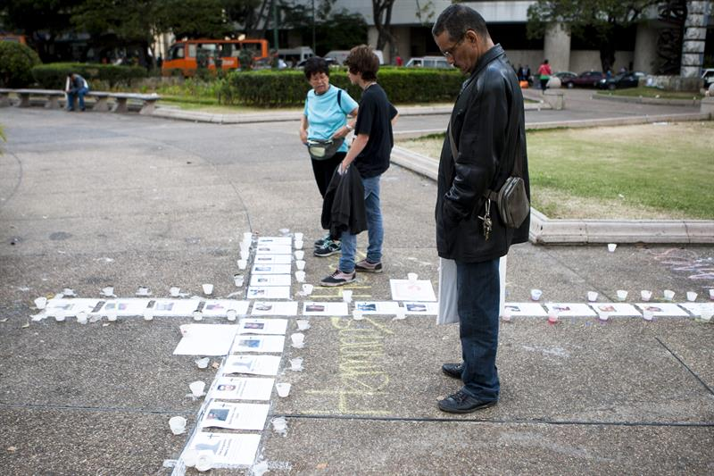 People made a cross in the ground with the pictures of the dead during the protests in Venezuela.