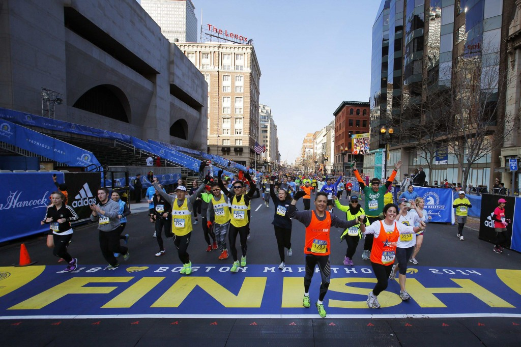 Race fans cheer near the finish line at the 118th Boston Marathon on Monday. The race began with a moment of silence for those killed and injured in the bombing attacks during the event a year ago.