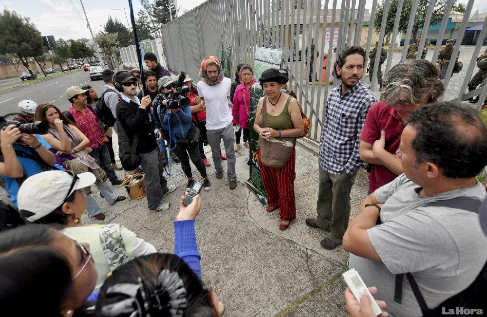 Members of YASunidos wait outside the Army's former grocery store.
