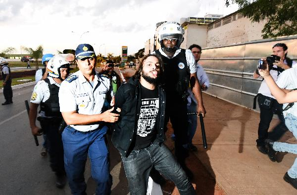 Riot police arrest an activist who smashed a police car with a stone