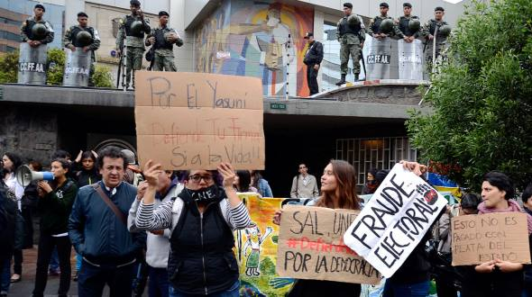 Members of the YASunidos group protest outside the CNE, while uniformed police members guard the entrance.