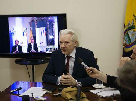 Julian Assange speaks to journalists from the Ecuadorian Embassy in London (AFP)
