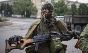 An armed pro-Russian separatist looks on at a town center in Snizhnye in eastern Ukraine