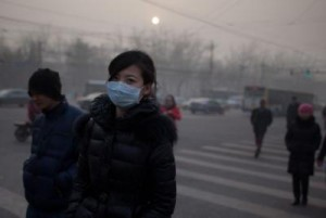 A woman wearing a mask crosses a road during severe pollution in Beij