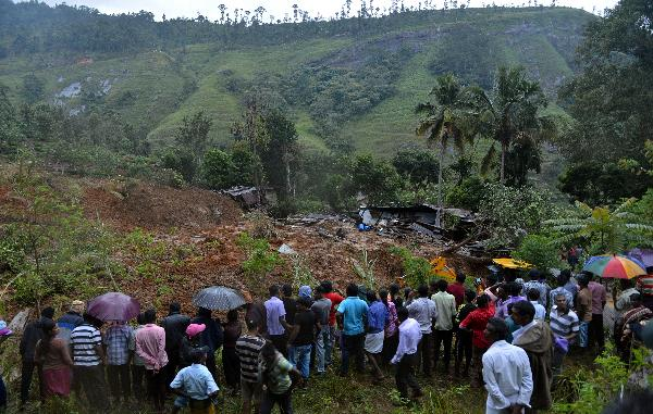 Sri Lankan residents stand near a damaged building at the site of a landslide caused by heavy monsoon rains in Koslanda village in central Sri Lanka on October 29, 2014. Mudslides triggered by monsoon rains swept through a tea-growing region of Sri Lanka October 29, killing at least 16 people and leaving about 300 more feared missing.