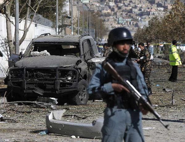 Afghan security forces inspect the site of a suicide attack in Kabu