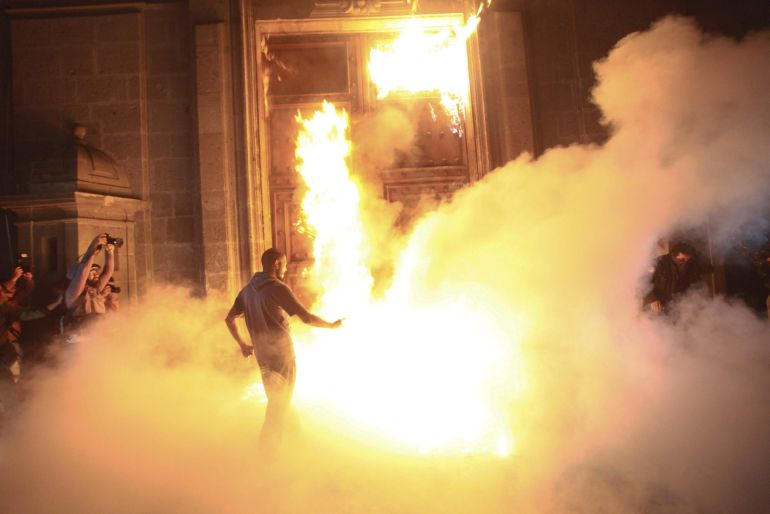 Protesters burning the Mexican National Palace door / Sásheka Gutierrez (EFE)