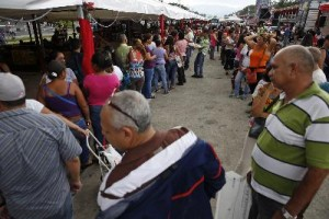 People stand in line to buy food at a state-run street market in Caracas