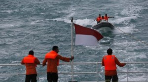 Rescue team members in a boat communicate with other members of the team on the deck of the SAR ship KN Purworejo during a search operation for passengers onboard AirAsia Flight QZ8501 in the Java Sea
