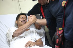 """Pablo Rafael Cordova Ca""""izares shakes hands with one of the Colombian firefighters who rescued him, at the Verdi Cevallos Balda hospital in Portoviejo, Ecuador, Monday, April 18, 2016. The 51-year-old hotel administrator was one of a trickle of survivors pulled from the rubble after Ecuador's strongest earthquake in decades flattened towns along the coast and killed hundreds. (AP Photo/Emilio D. Garcia) -----"""