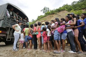 Victims of the 7.8 magnitude earthquake line up to get emergency food and clothing from an army truck in Cholote, Ecuador, Thursday, April 21, 2016. The victims walked 45 minutes to make it to the collection point arranged by Ecuadorís armed forces. President Rafael Correa said Ecuador's worst earthquake in decades caused billions of dollars of damage and he is raising sales taxes and putting a one-time levy on millionaires to help pay for reconstruction. (AP Photo/Dolores Ochoa) -----