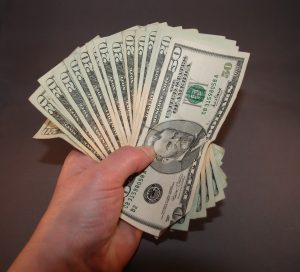 Large bills fanned out and held in hand